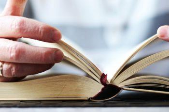 Hands holding open a book.