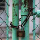 Padlock on green gate.