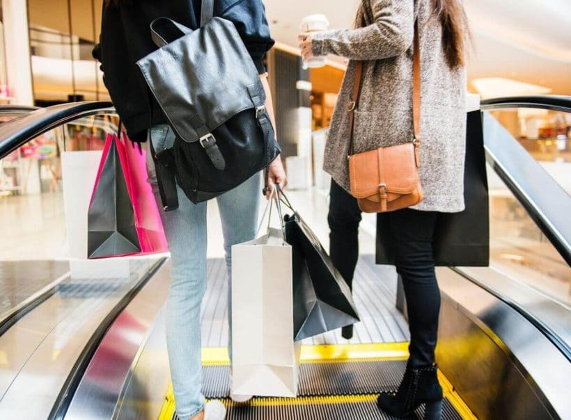 Women with shopping bags on an escalator
